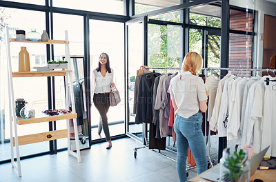 Buy stock photo Shot of two young women shopping in a clothing store