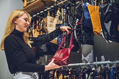 Buy stock photo Shot of a young woman shopping for handbags at a store