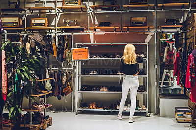 Buy stock photo Rearview shot of a young woman shopping for shoes at a store