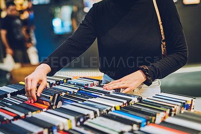 Buy stock photo Cropped shot of a young woman shopping for DVDs at a store