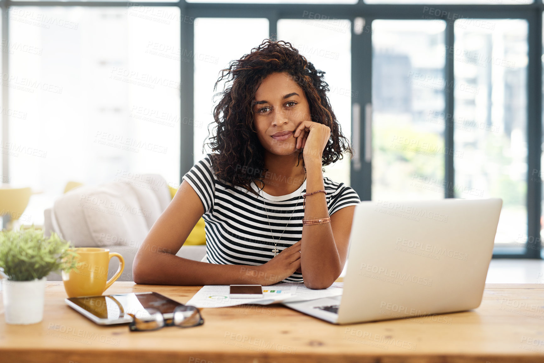 Buy stock photo Cropped portrait of an attractive young businesswoman sitting alone and working from home during the day