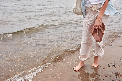 Buy stock photo Cropped shot of an unrecognizable woman going for a walk along the waters edge of a lake