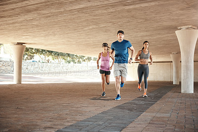 Buy stock photo Shot of a small group of three people out for a run together