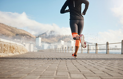 Buy stock photo Shot of an unrecognizable woman out for a run on the promenade