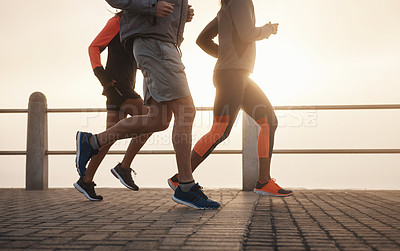 Buy stock photo Shot of a small group of three people out for a run together on the promenade
