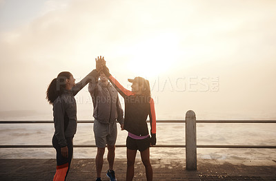 Buy stock photo Shot of a small group of three people giving each other a high five while out for a workout