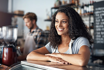Buy stock photo Defocused shot of a young shop owner looking happy while standing in her cafe
