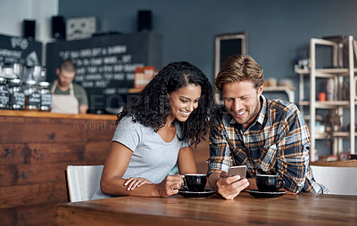 Buy stock photo Shot of a couple looking at something on a cellphone while sitting in a coffee shop