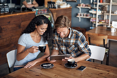 Buy stock photo Shot of a couple looking at something on a digital tablet while sitting in a coffee shop