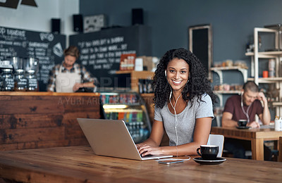 Buy stock photo Shot of a woman wearing earphones while using her laptop in a cafe