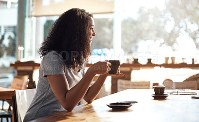 Buy stock photo Cropped shot of a young woman enjoying a cup of coffee at a cafe