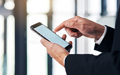 Buy stock photo Cropped shot of an unrecognisable businessmen using a smartphone in a modern office