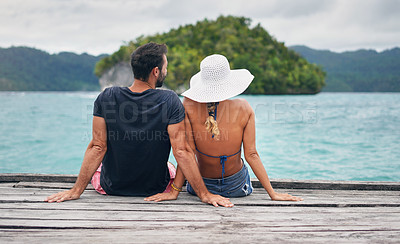 Buy stock photo Rearview shot of an unrecognizable couple sitting together on a boardwalk overlooking the ocean during vacation