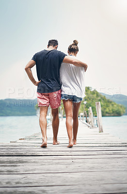 Buy stock photo Rearview shot of an unrecognizable couple walking along the boardwalk together during a vacation in Indonesia