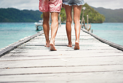 Buy stock photo Rearview shot of an unrecognizable couple walking down a boardwalk overlooking the ocean during a vacation