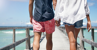 Buy stock photo Rearview shot of an unrecognizable couple walking down a boardwalk and holding hands during a vacation