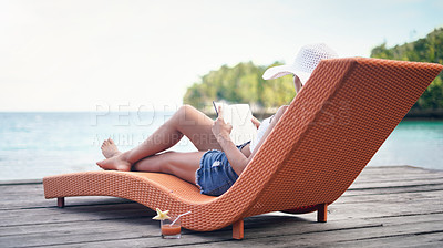 Buy stock photo Full length shot of an attractive young woman sitting on a sun lounger and reading a book during a vacation