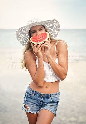 Buy stock photo Cropped portrait of an attractive young woman standing and playfully holding up a watermelon piece during a vacation