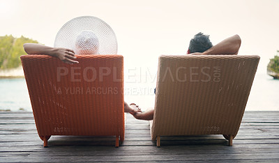 Buy stock photo Rearview shot of an unrecognizable couple sitting on sun loungers together and holding hands while on vacation