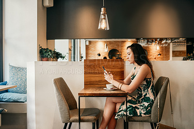 Buy stock photo Cropped shot of an attractive young woman sitting alone in a coffee shop and texting on her cellphone