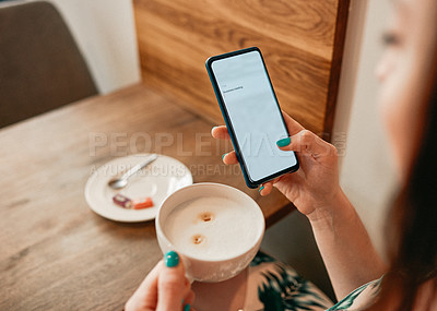 Buy stock photo Cropped shot of an unrecognizable woman sitting in a cafe and using her cellphone while holding a cup of coffee
