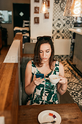 Buy stock photo Cropped shot of an attractive young woman using her cellphone and holding a cup of coffee in a cafe