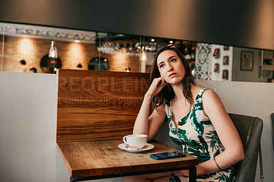 Buy stock photo Cropped shot of an attractive young woman sitting in a coffee shop alone and looking contemplative