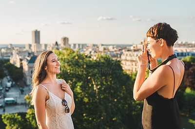 Buy stock photo Cropped shot of an attractive young woman photographing her female friend using a camera while sightseeing in a foreign city