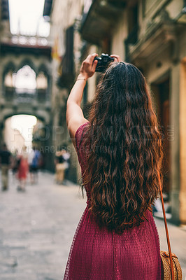 Buy stock photo Rearview shot of an unrecognizable woman standing alone and taking pictures with her camera while sightseeing in Spain