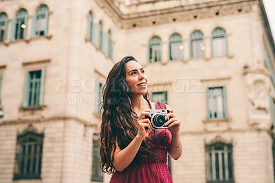 Buy stock photo Cropped shot of an attractive young woman standing alone and holding her camera while touring the streets of Spain