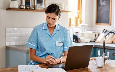 Buy stock photo Shot of a young nurse going through paperwork while working on a laptop in a nursing home