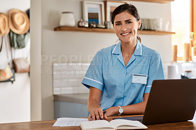 Buy stock photo Portrait of a young nurse writing notes while working on a laptop in a nursing home