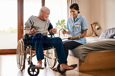 Buy stock photo Shot of a young nurse checking a senior man's blood pressure in a retirement home