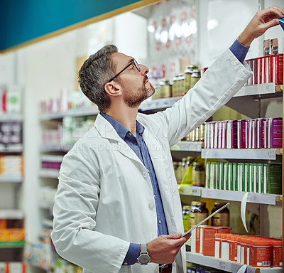 Buy stock photo Shot of a pharmacist holding a digital tablet while reaching for medication on a shelf