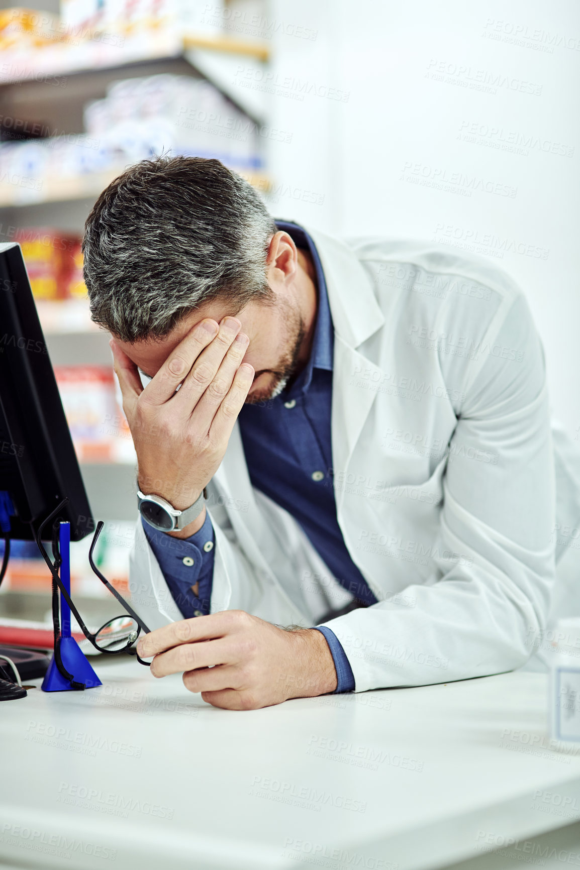 Buy stock photo Cropped shot of a male pharmacist looking stressed at work