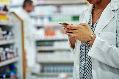 Buy stock photo Cropped shot of a female pharmacist using her cellphone
