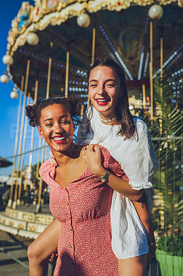 Buy stock photo Shot of two happy young women enjoying a piggyback ride at a carnival