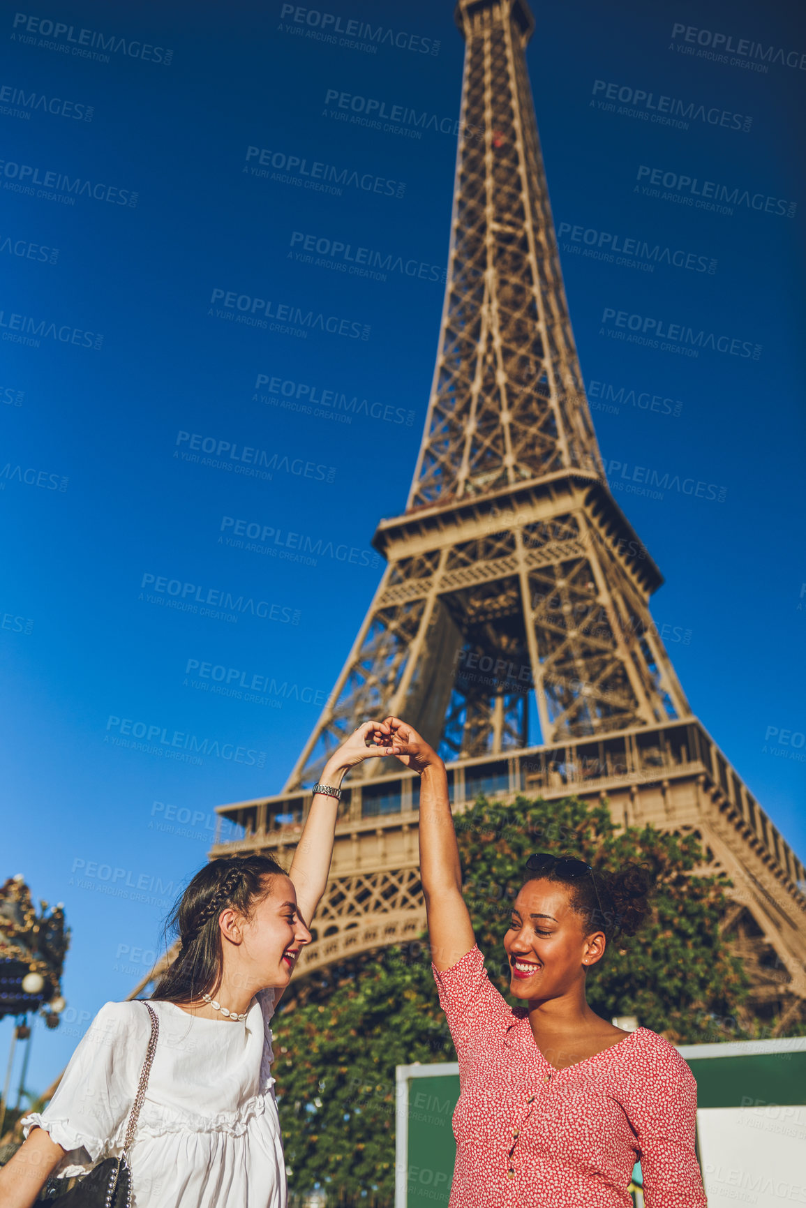 Buy stock photo Shot of two happy young women making a heart shaped gesture with their hands at a carnival