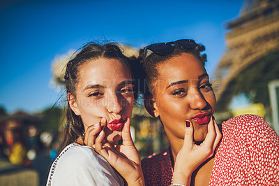 Buy stock photo Shot of two happy young women sharing a playful moment at the carnival