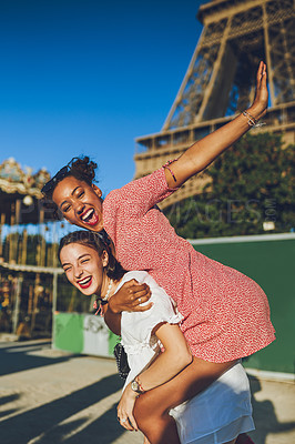 Buy stock photo Shot of two happy young women enjoying a piggyback ride at a carnival.