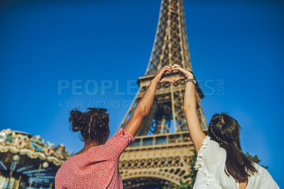 Buy stock photo Rearview shot of two young women making a heart shaped gesture with their hands at a carnival