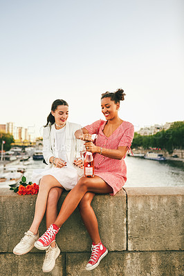 Buy stock photo Full length shot of two attractive young women sitting and drinking wine together alongside a canal in Paris, France