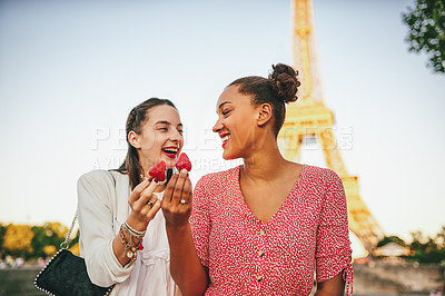 Buy stock photo Shot of two attractive young women eating strawberries together outdoors in Paris with the Eiffel Tower in the background