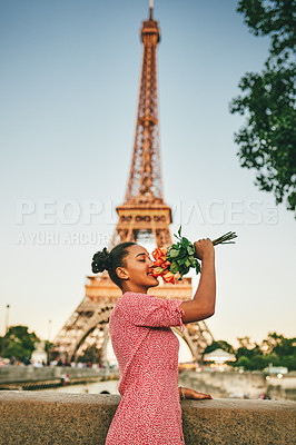 Buy stock photo Shot of an attractive young woman smelling a bouquet of roses outdoors in Paris with the Eiffel Tower in the background
