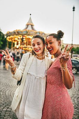 Buy stock photo Portrait of two attractive young woman posing together outside a carnival in Paris, France
