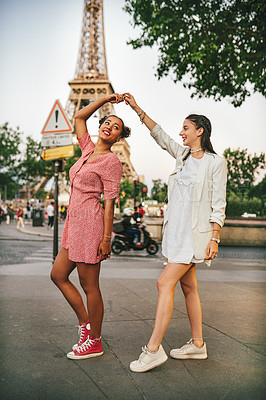Buy stock photo Full length shot of two attractive young women dancing together in the city streets of Paris, France