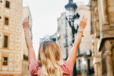 Buy stock photo Rearview shot of an unrecognizable woman standing with her arms raised while touring Barcelona alone