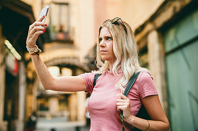 Buy stock photo Cropped shot of an attractive young woman standing alone and holding up her cellphone for a selfie while on holiday