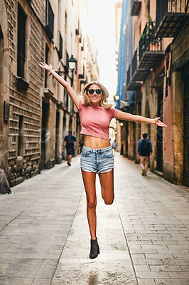Buy stock photo Full length portrait of an attractive young woman jumping for joy while touring the streets of Barcelona during a holiday