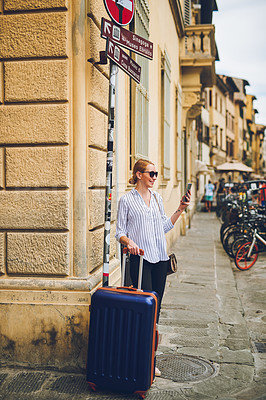 Buy stock photo Shot of a woman walking with a suitcase in a foreign city